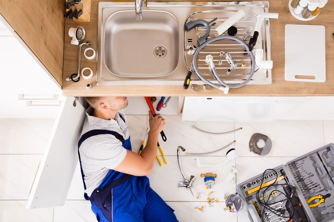 A plumber making repairs under a kitchen sink
